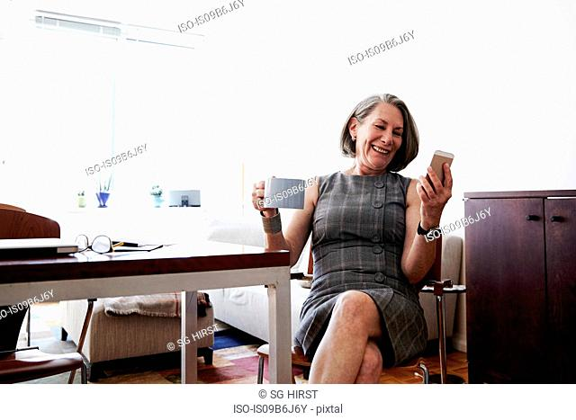 Senior businesswoman sitting at desk, holding coffee cup, looking at smartphone, laughing