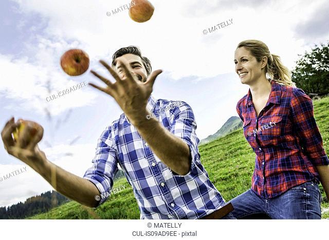 Woman looking at man juggling apples