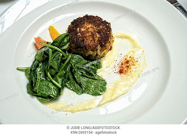 Crabmeat Cake and Tossed Spinich Salad, garnished with a Citrus Sauce, Served on a White China Plate in a New York City Restaurant