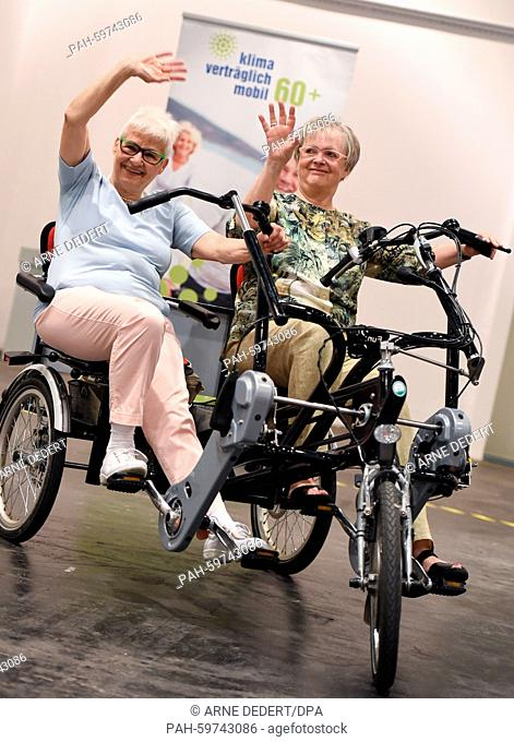 Gunda Krauss (l) and Rosemarie Killius drive a parallel tandem bicycle on a test course at the fair of the elderly, SenNova