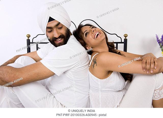 Sikh couple sitting back to back on the bed