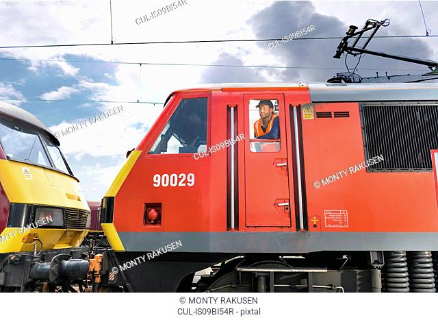 Train driver in locomotive cab in train engineering factory