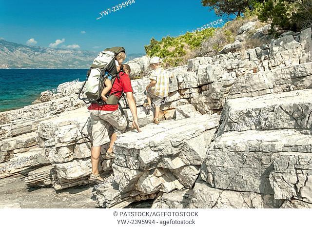 Father trekking with children on a rocky coast of Kabal peninsula, Hvar island, Croatia