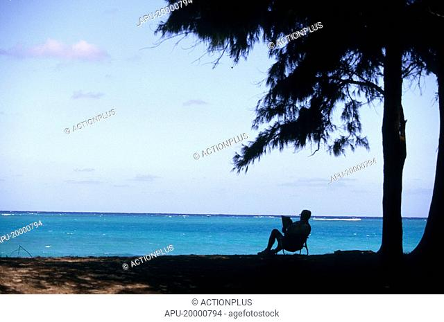 Man sitting in a shaded chair at the beach