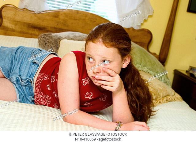 Preteen redhead girl, in Connecticut, USA, reclining on her mother's bed, thinking