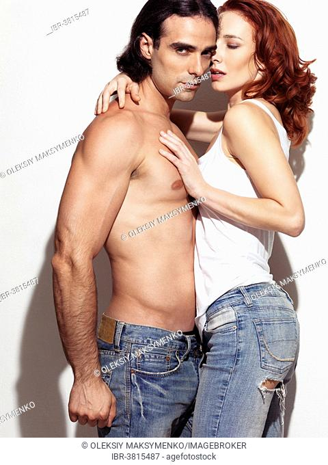Young man with bare torso wearing jeans is embraced by a red-haired woman