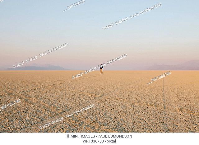 The figure of a man in the empty desert landscape of Black Rock desert, Nevada