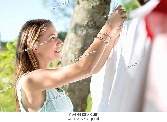 Smiling young woman hanging laundry on clothesline
