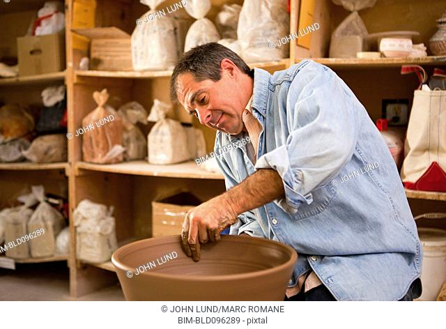 Caucasian man making pottery bowl