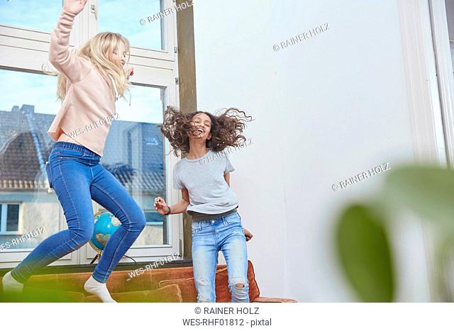 Two enthusiastic girls jumping and dancing at home