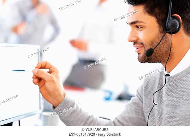 Business man using headset and pointing at computer with colleagues in background