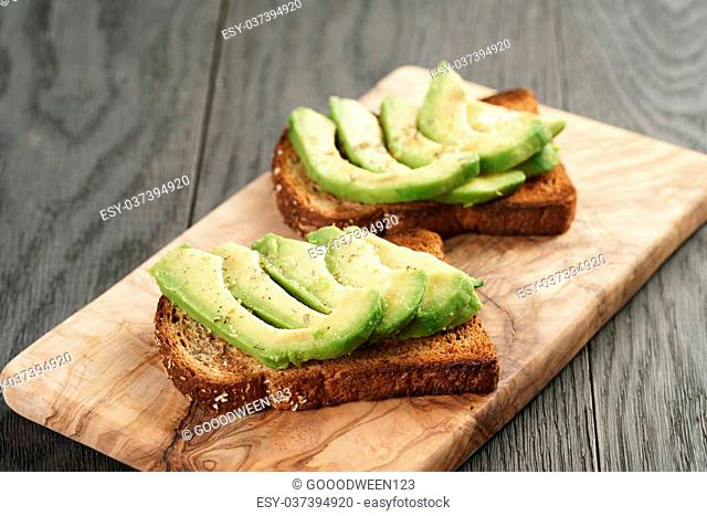 toasted rye bread with sliced avocado and herbs, simple rustic sandwich