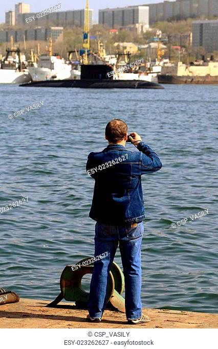 a man takes pictures of a submarine