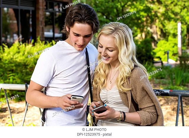 A young couple stands together on the university campus looking at their smart phones to show each other social media posts; Edmonton, Alberta, Canada
