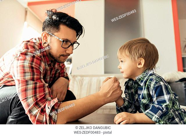Father and son arm wrestling