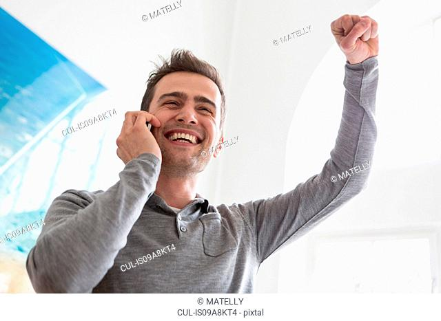 Mature man on telephone call, arm raised