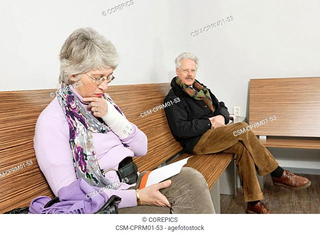 two elderly people sitting in a general practitioner's waiting room, reading various magazines and newspapers