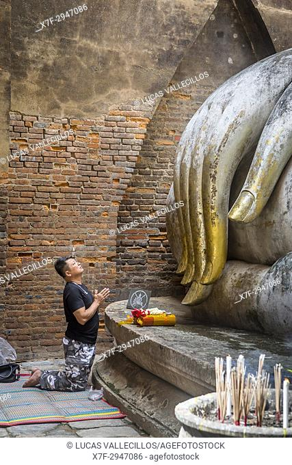 Man praying, Wat Si Chum, in Sukhothai historical park, Sukhothai, Thailand