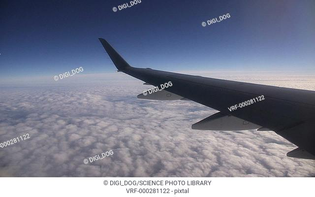 Aerial footage of part of an aeroplane wing above the clouds in the sky