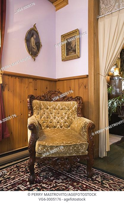 Rococo style chair in a parlor room inside an old 1904 Victorian cottage style residential home, Quebec, Canada. This image is property released