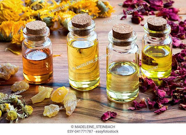 Bottles of essential oil with dried rose petals, chamomile, calendula and frankincense on a wooden table