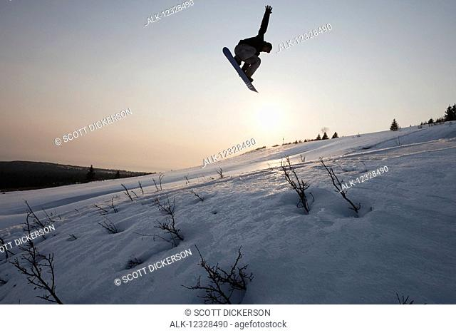 Silhouette of a snowboarder in mid-jump, South-central Alaska, Homer, Alaska, United States of America