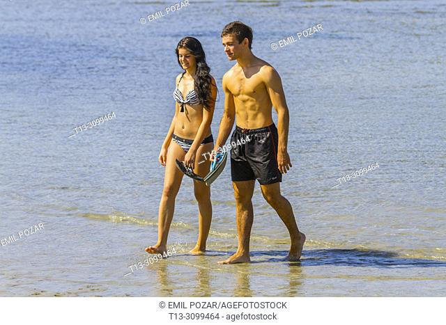 Young couple Summer vacation walking along beach