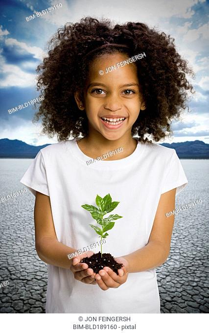 African girl holding seedling in desert
