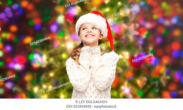 christmas, winter, holidays and childhood concept - dreaming girl in santa helper hat over glitter or lights background