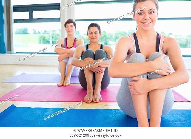 Smiling women sitting on yoga mats in fitness studio