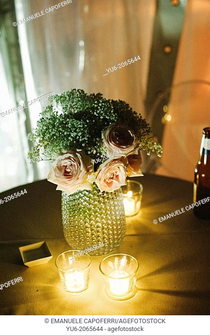 Table with candles and flower composition