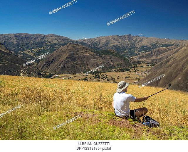A man takes a selfie with his selfie-stick while resting during a hike in the foothills of the Andes Mountains; Cusco, Peru