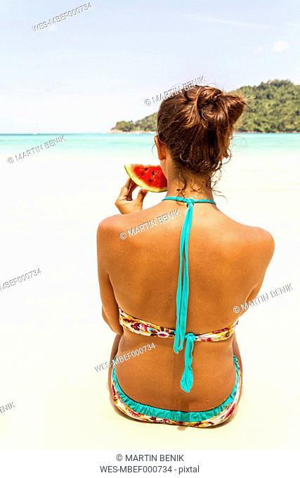 Thailand, Koh Surin island, woman eating a slice of watermelon at the white sandy beach