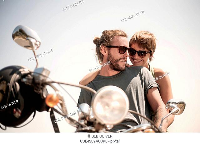 Portrait of couple sitting on moped