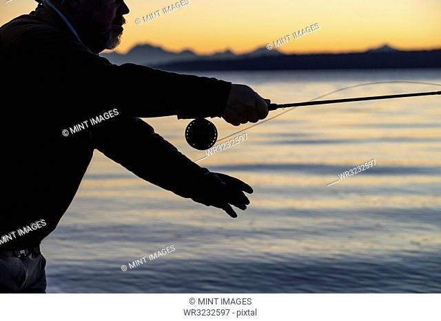 A silhouette of a fly fisherman casting at sunrise for searun coastal cutthroat trout on a beach on the west coast of the USA