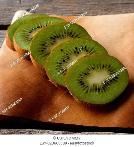 Kiwi slices on brown paper