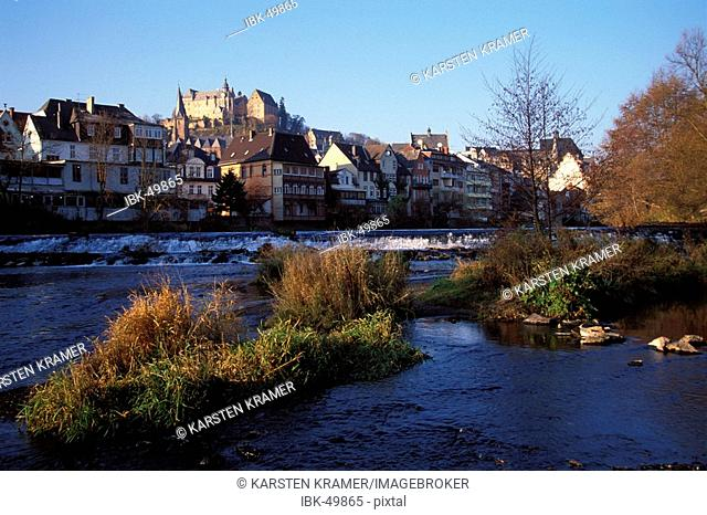 Marburg at the Lahn river, view of the pitoresque small town from the river coastline in late autumn, in the mittle on the mountain top the old castle