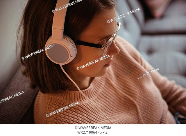Woman sitting on sofa listening to music on headphone in living room