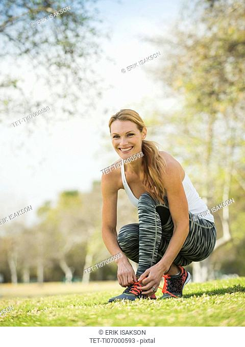 Woman in park tying shoe
