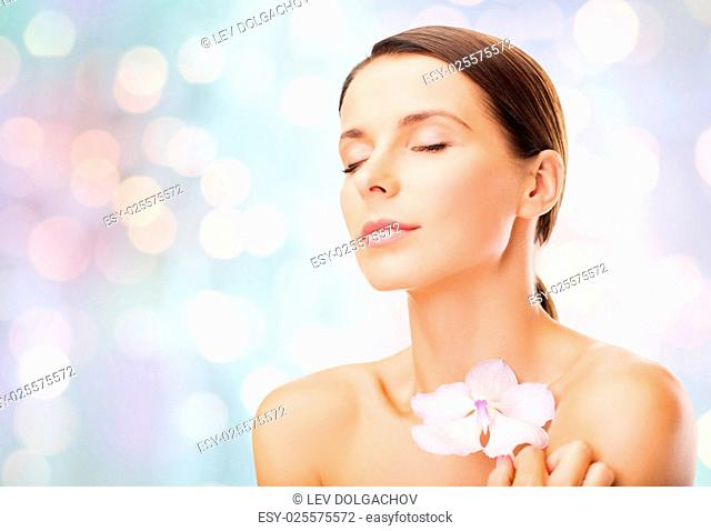 beauty, people, bodycare and health concept - beautiful young woman with orchid flower and bare shoulders over holidays lights background