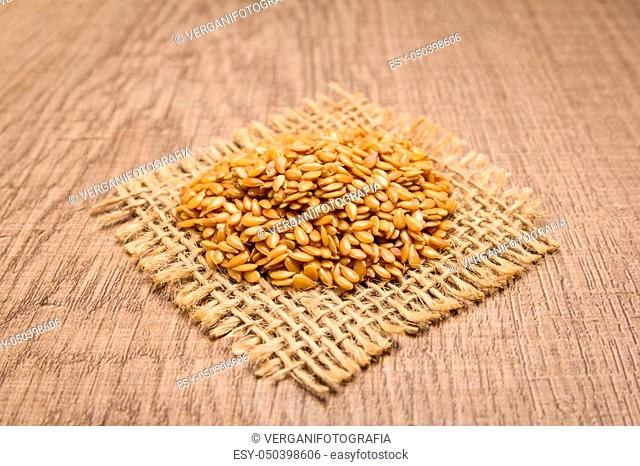 Linum usitatissimum is scientific name of Golden Flax seed. Also known as Linseed, Flaxseed and Common Flax. Grains on square cutout of jute