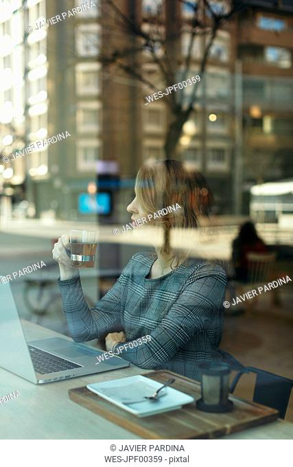 Mature businesswoman with glass of tea laptop in a cafe