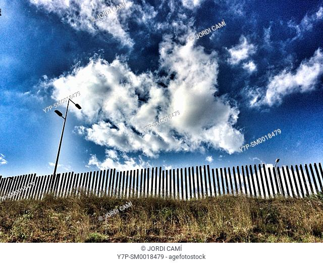 Cloudy blue sky and fence