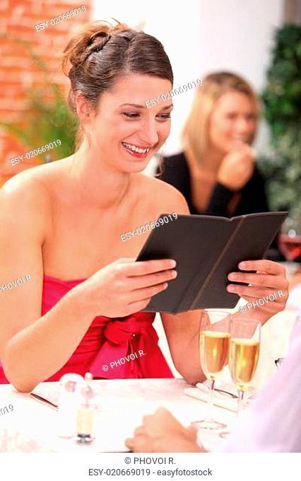 woman looking at the menu at a restaurant