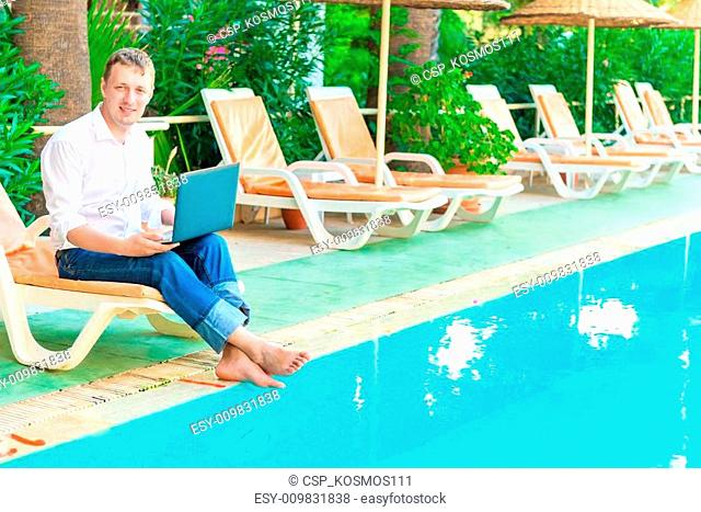 Manager with a laptop smiling and working
