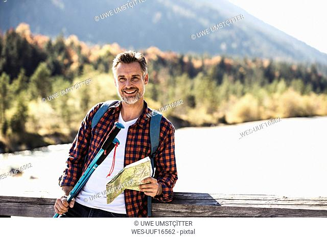 Austria, Alps, smiling man on a hiking trip with map on a bridge