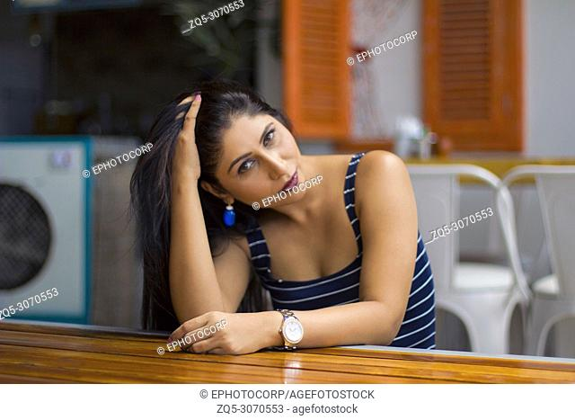 Young, beautiful Indian girl in blue half sleeve sitting and posing with her hands in hair
