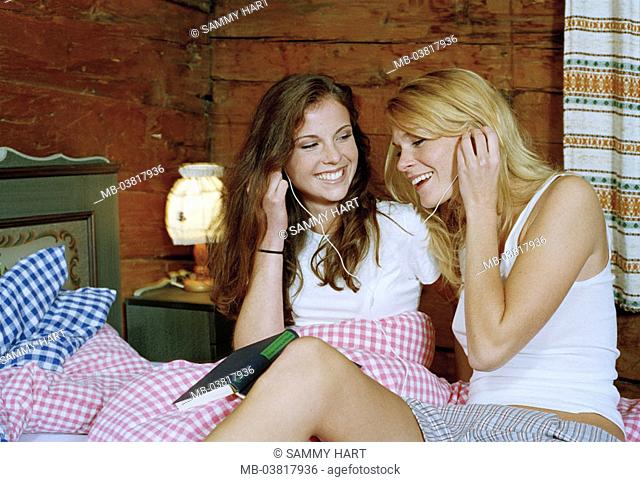 Almhütte, women, two, young, underwear,  Bed, lie, book, headphones, music hearing,  together, cheerfully, laughing,  Series, friends, 20-30 years, blond