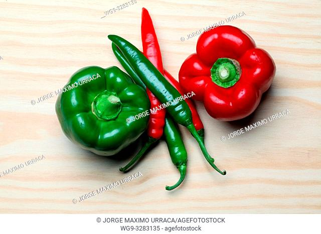 Green and Red peppers and chilli peppers on kitchen table