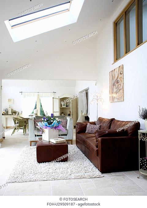 Brown leather sofa and ottoman in large white living room with cream cotton rug